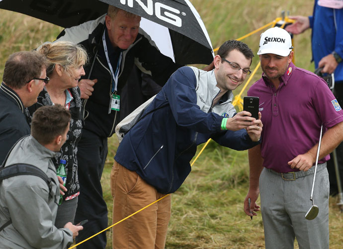 A spectator takes a photo with Graeme McDowell along the 13th fairway.