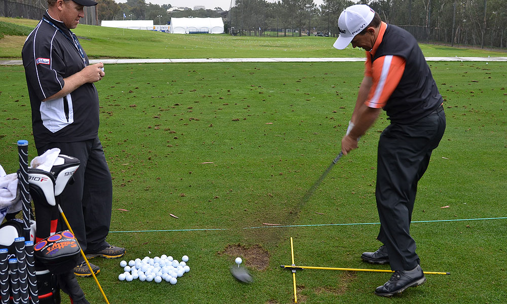 Greg Chalmers worked on his alignment using two sticks and his caddie's keen eyes.