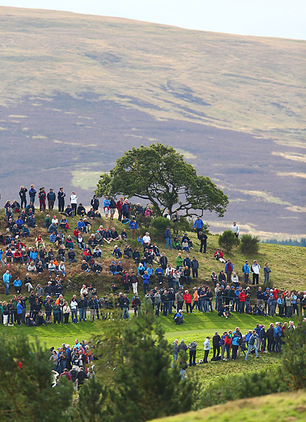 Dozens of spectators watch the Thursday practice rounds from a hill on the course.