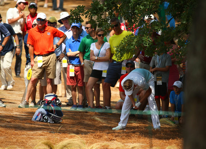 Ian Poulter examines his lie in the pine straw during his second round 74. He's tied for 23rd at +4.