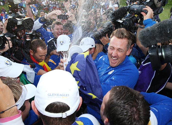 Ian Poulter starts the champagne shower as his teammates gather to start celebrating their win.