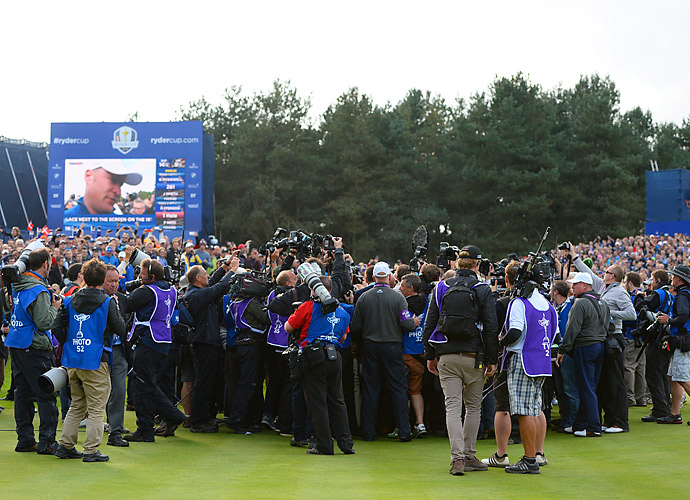 The media swarms Jamie Donaldson after he earned the clinching point on Sunday.