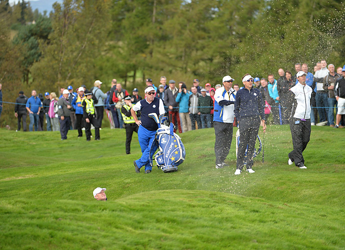 Jamie Donaldson hits a bunker shot with teammate Ian Poulter looking on.