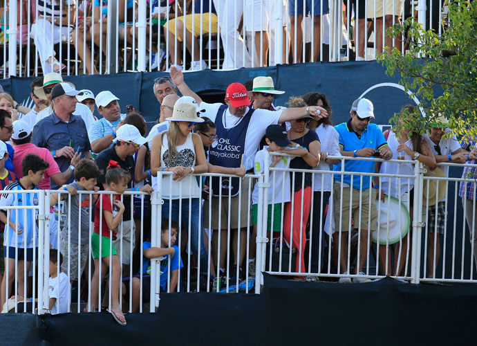 Jason Bohn's caddie drops his ball down from the stands on the 18th green.