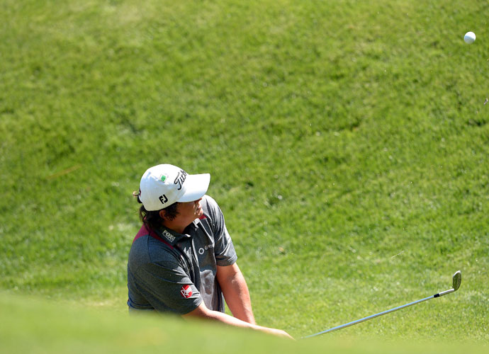 Jason Dufner chips out of the creek on the par-5 13th hole. He made a 9 and shot 80 after making the turn at even par.