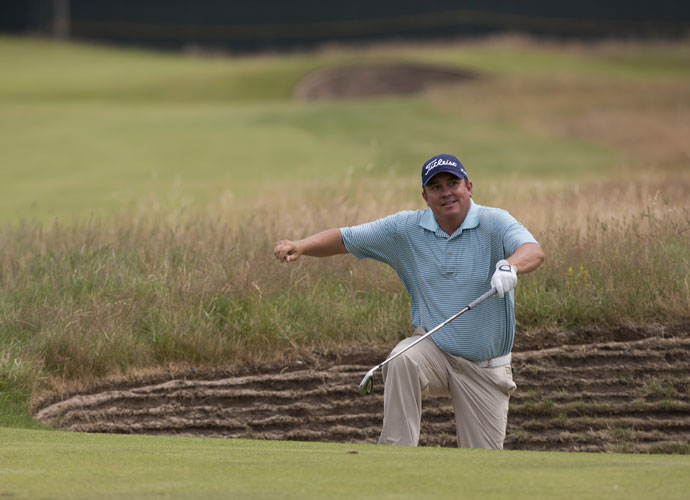 Jason Dufner climbs out of a bunker on the second fairway during his Saturday practice round.