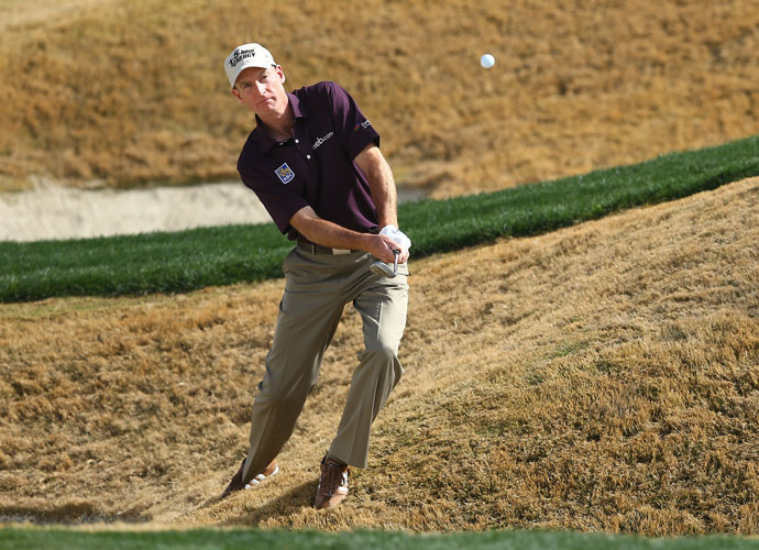 Jim Furyk leans into a shot from a tough lie during his 1-up win over Harris English.