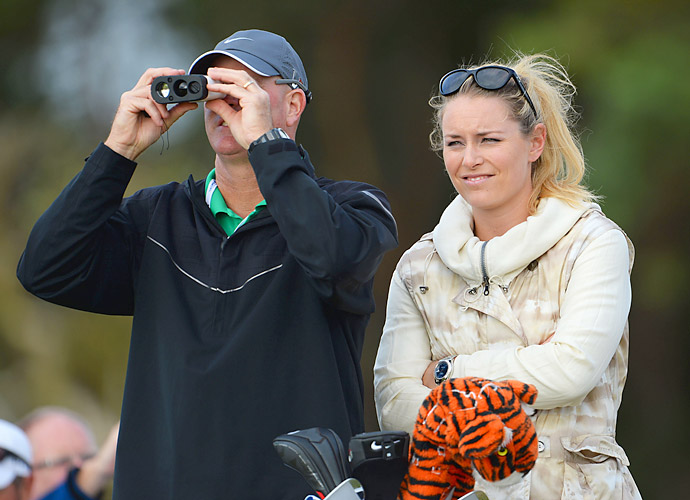 Vonn and Woods' caddie Joe LaCava observe Woods practicing on Monday.