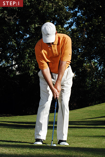 STEP 1                             Set up with your weight even over both feet and the ball just forward of center. Set your hands slightly behind the ball (you'll need this position at impact, too).