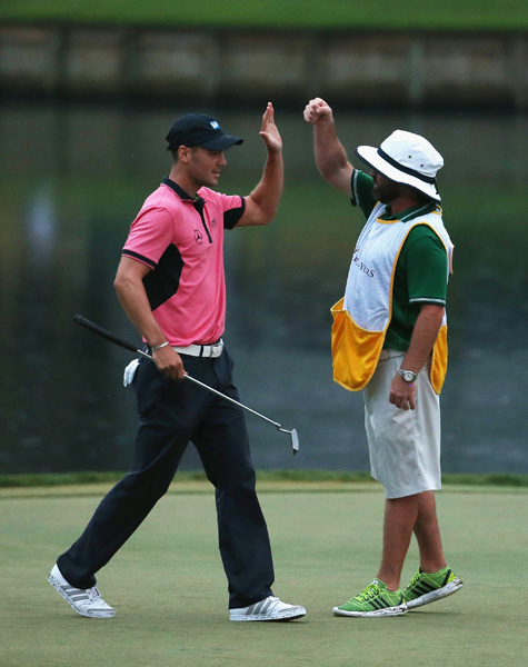 Kaymer celebrates with his caddie Craig Connelly after draining a crucial 28-foot par-saving putt on the island-green 17th to preserve his lead.