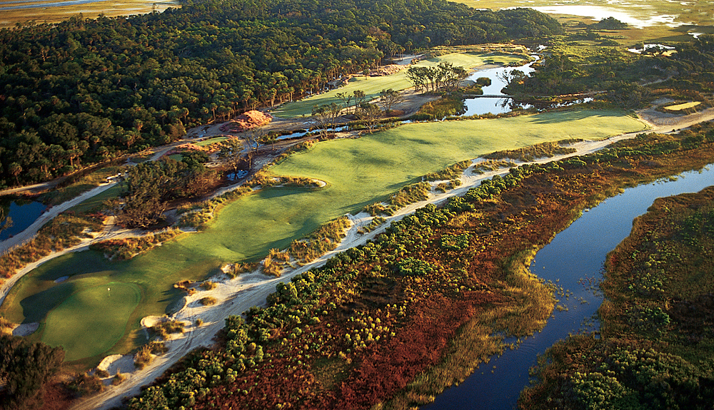 "Hole 9, 494 yards, Par 4                       The outward nine ends on a demanding two-shotter surrounded by trouble. ""The big deal on this hole is that the green is a little bit offset, so the ball has to be turning right to left on the second shot or they'll have to carry it to the green,"" says architect Pete Dye. On a fast, windy day, that might mean a third from the deep pot bunker over the green. (Source: KiawahResort.com)"
