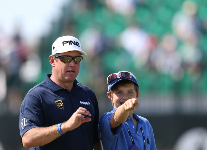Lee Westwood walks with his son along the fourth fairway.