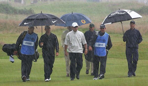 Davis Love (far right) and Justin Leonard (second from left) felt the wrath of rain and wind Wednesday as they practiced.