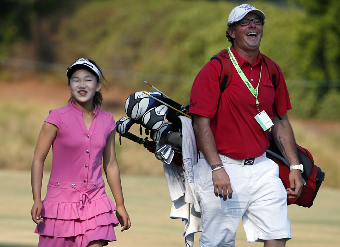 Lucy Li shares a laugh with her caddie as they walk to the second green.