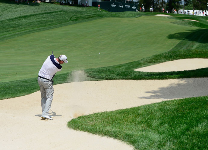 Marc Leishman hits out of a fairway bunker on the 15th hole. The Australian shot 66 and was part of a three-way tie for the lead with Ricky Barnes and Oliver Goss.