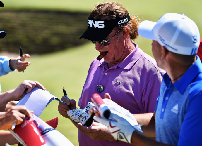 Miguel Angel Jimenez and Sergio Garcia sign autographs during their practice round.