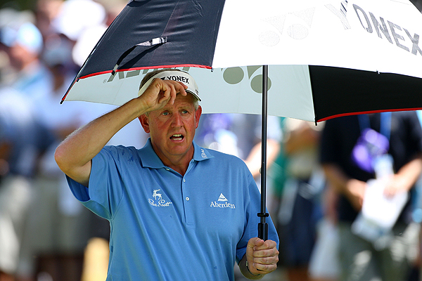 Colin Montgomerie sought refuge from the sun under his umbrella. He made the cut on the number at five over.
