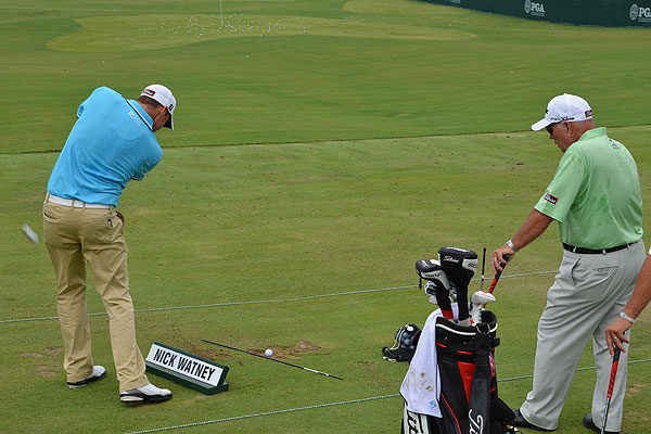 Nick Watney turned a sign into a training aid on Tuesday as Butch Harmon looked on. Watney is using Titleist's new 712 AP2 irons.