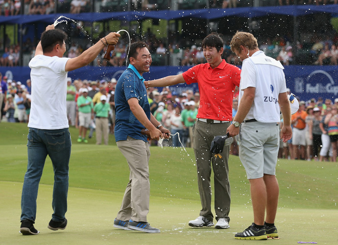 Noh celebrates on the 18th green with his caddy Scott Saitinac and golfers Charlie Wi and Y.E. Yang.