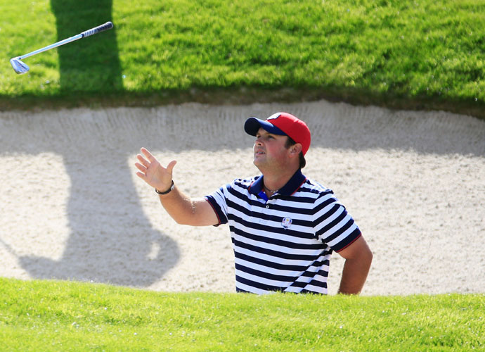 Patrick Reed tosses his club in the air after playing from a bunker on the third hole.