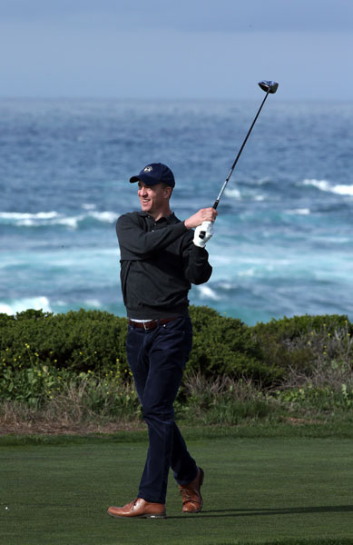 Denver Broncos quarterback Peyton Manning hits a tee shot on the 13th hole during the first round.