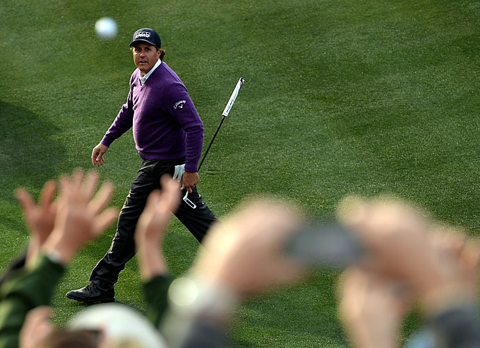 Phil Mickelson watches the flight of a ball he threw to fans on the 16th hole during the second round of the Waste Management Phoenix Open.