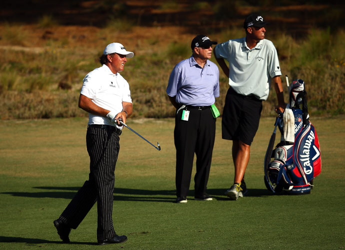 "Butch Harmon and Jim ""Bones"" Mackay watch Phil Mickelson hit an approach during a pre-tournament practice round."