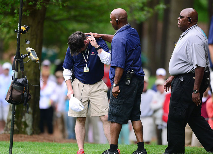 A course worker (left) is attended to after being hit by a Phil Mickelson drive on the fifth hole.