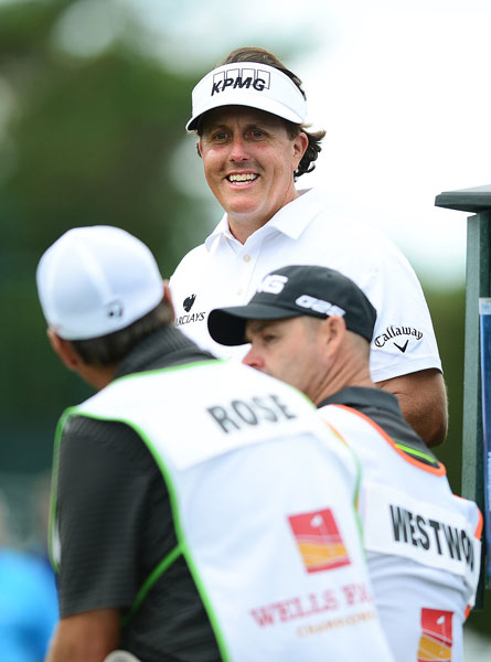 Phil Mickelson jokes with the caddies of playing partners Lee Westwood and Justin Rose.