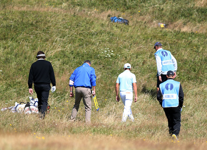 Phil Mickelson (left) gets help from Rickie Fowler (center) to find an errant shot off the 14th fairway.
