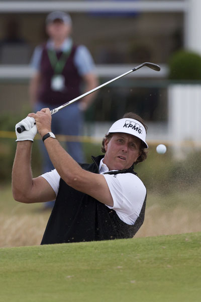 Phil Mickelson plays out of a bunker to the second green during his practice round.