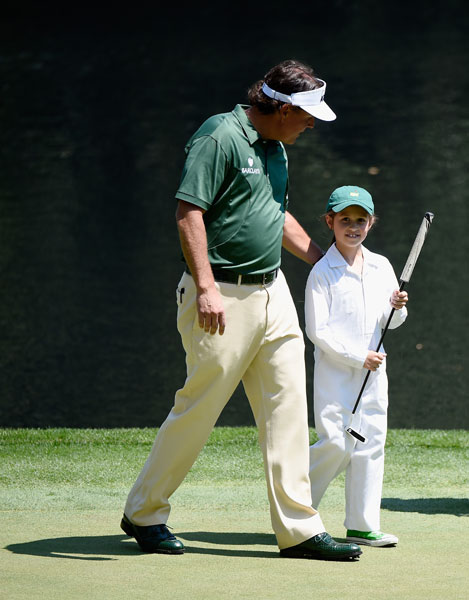 Phil Mickelson walks across the ninth green with Emma Mackay, daughter of Phil's caddie Jim.