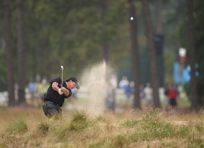 Phil Mickelson blasts from a waste area on the 12th hole.