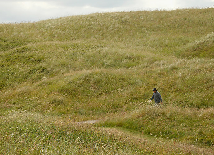 Phil Mickelson walks through the dunes on the fourth hole.
