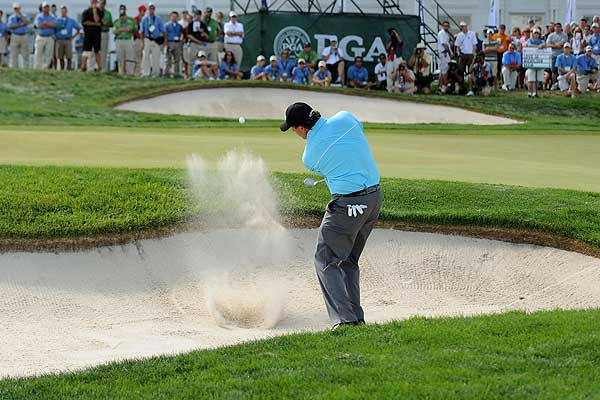 Mickelson had his caddie pull the pin before he hit this bunker shot on the ninth hole. Bogeying three of his final five holes led to a Friday 73 for Mickelson.