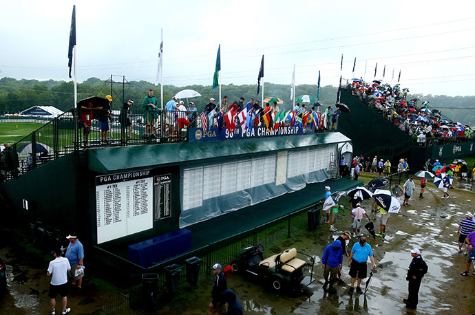 Fans walk in the rain near the practice range during a weather-delayed final round of the 96th PGA Championship at Valhalla Golf Club