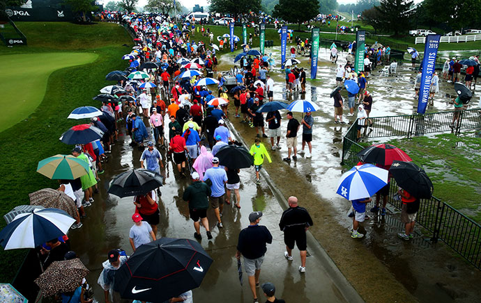 Fans walk in the rain near the practice range during a weather-delayed final round of the 96th PGA Championship at Valhalla Golf Club.