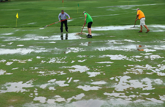 Members of the grounds crew squeegee the practice ground during a weather-delayed final round of the 96th PGA Championship at Valhalla Golf Club.