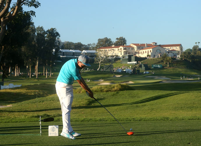 Rickie Fowler hits a tee shot on the ninth hole in view of the historic Riviera Country Club clubhouse. He shot a 3-under 68, two shots back of leader Dustin Johnson.