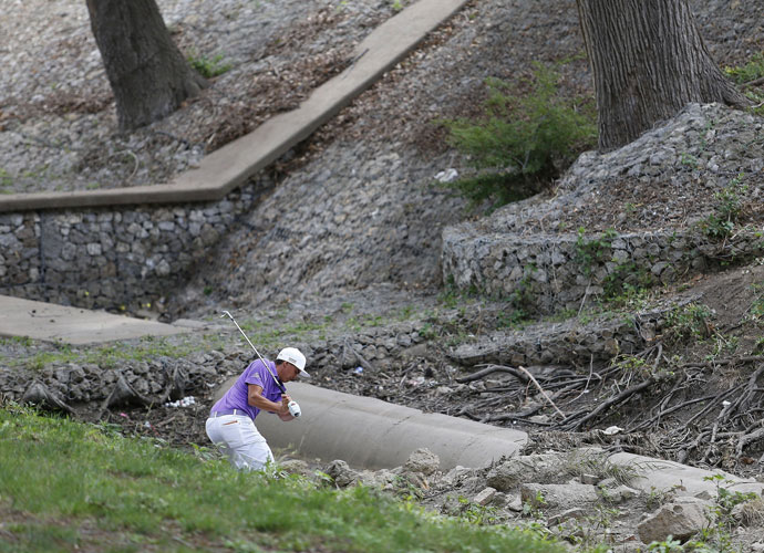 Rickie Fowler hits out of a creek after his tee shot on the 10th sailed wide right. He shot 80-75 and missed the cut.
