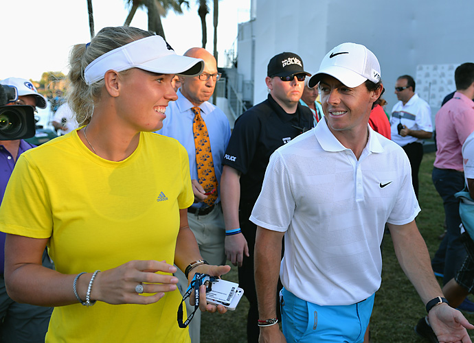 McIlroy walks off the course with his fiancee, Danish professional tennis player Caroline Wozniacki.
