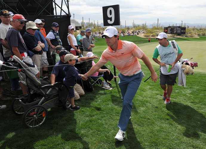 Rory McIlroy slaps hands with a young fan as he leaves the ninth green.