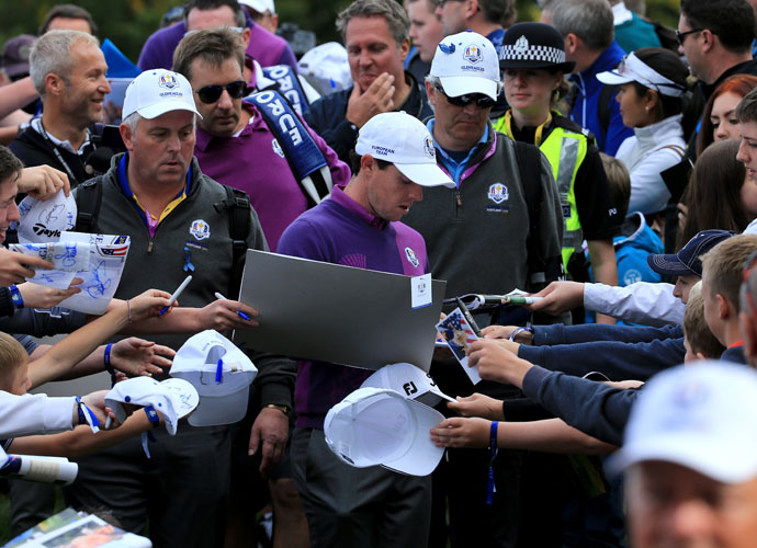 Rory McIlroy signs autographs during practice.