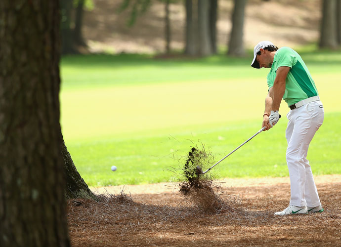 Rory McIlroy blasts out of the pine straw in the second round. McIlroy shot 76 and made the cut on the number.