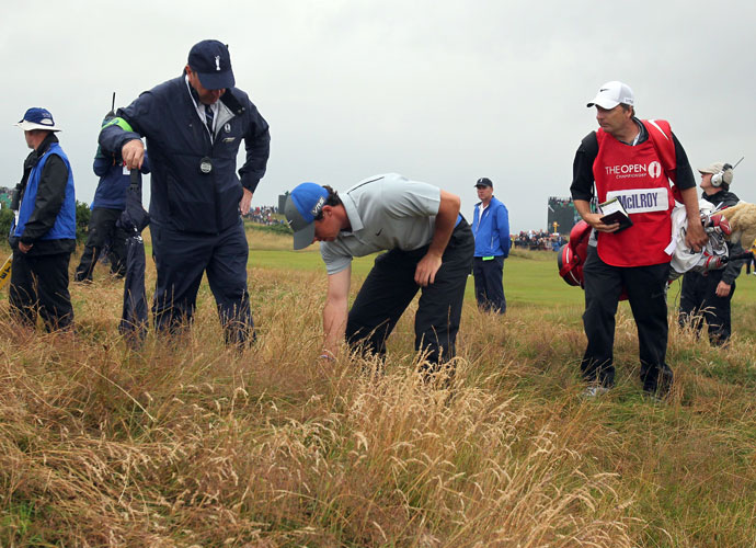 McIlroy looks for his ball in the rough on the 7th hole.