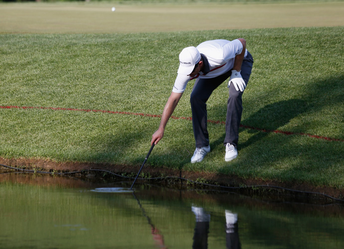 Rose fishes his ball out of the greenside water hazard.