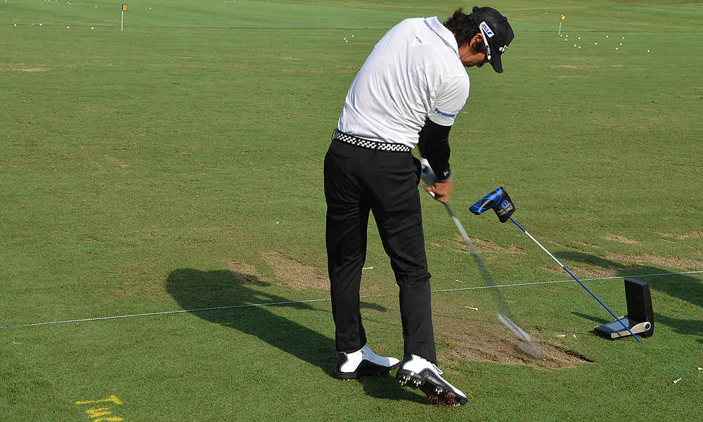 Ishikawa made a training aid out a shaft and a putter headcover.