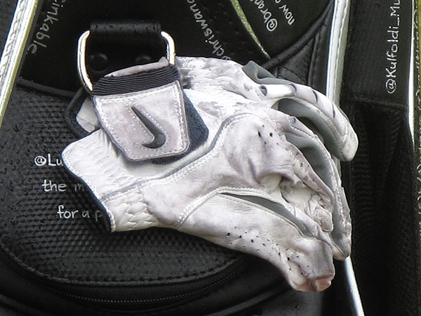 hung a weathered glove from his Tweet-covered golf bag Thursday.