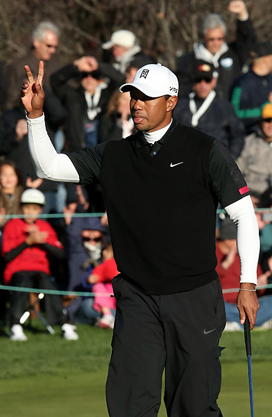 Woods acknowledges the crowd after his birdie putt on 18. He birded two of his last three holes.