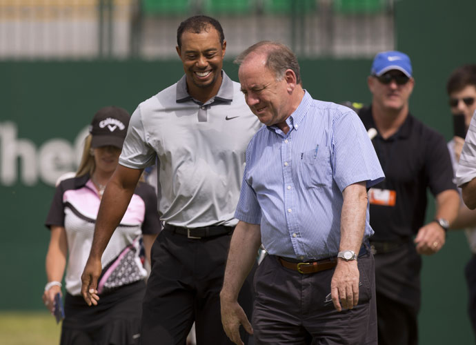 Tiger Woods laughs with Peter Dawson, Chief Executive of the R&A, on the first fairway during a practice round at Royal Liverpool.